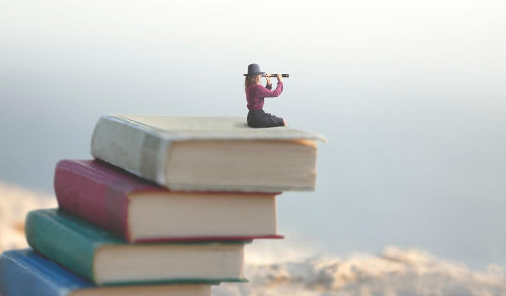Miniature woman looks with the spyglass